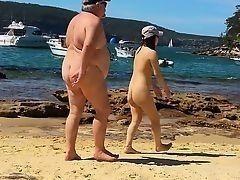 Толстый мужик преследует миниатюрную девушку на нуддистском пляже в Сиднее